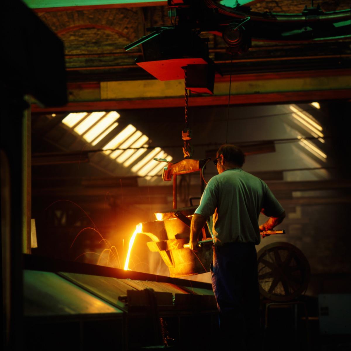 La photographie montre un fondeur au travail dans l'usine Godin SA de Guise.