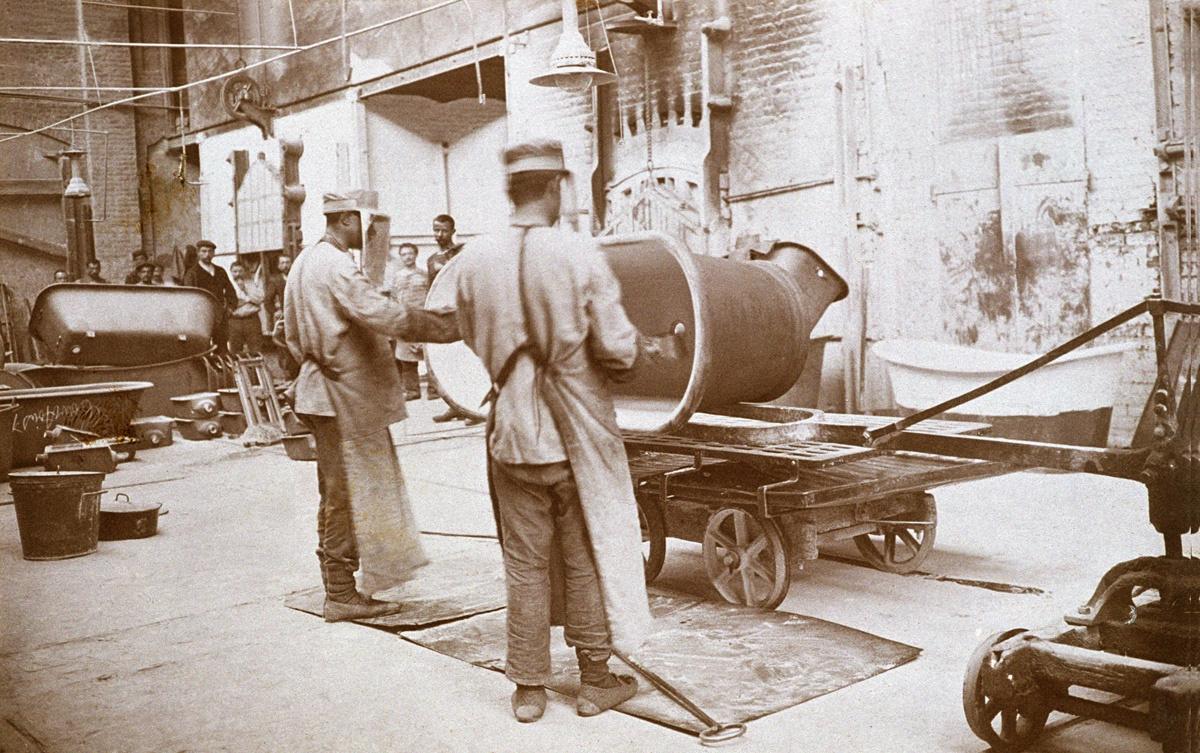 Sur la photographie, on voit deux ouvriers en train d'appliquer au pistolet sur