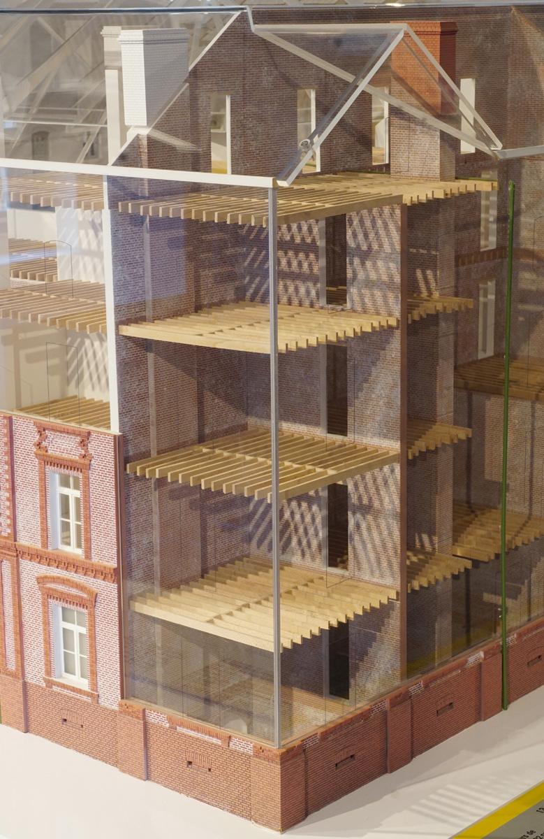 La photographie montre un écorché de la maquette sur le solivage des planchers
