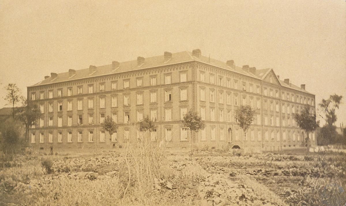 La photographie montre le pavillon Cambrai en arrière des jardins potagers