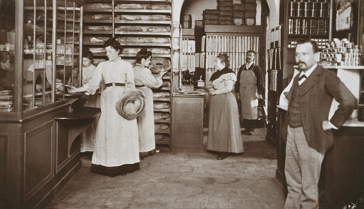 La photographie met en scène vendeurs et clientes dans l'épicerie.
