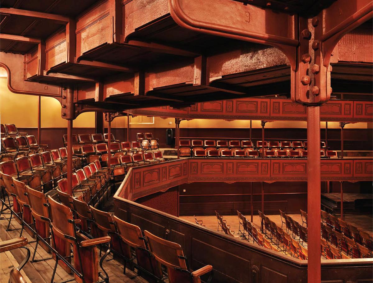 Le premier balcon du théâtre du Familistère, ses sièges en bois et tissu rouge.