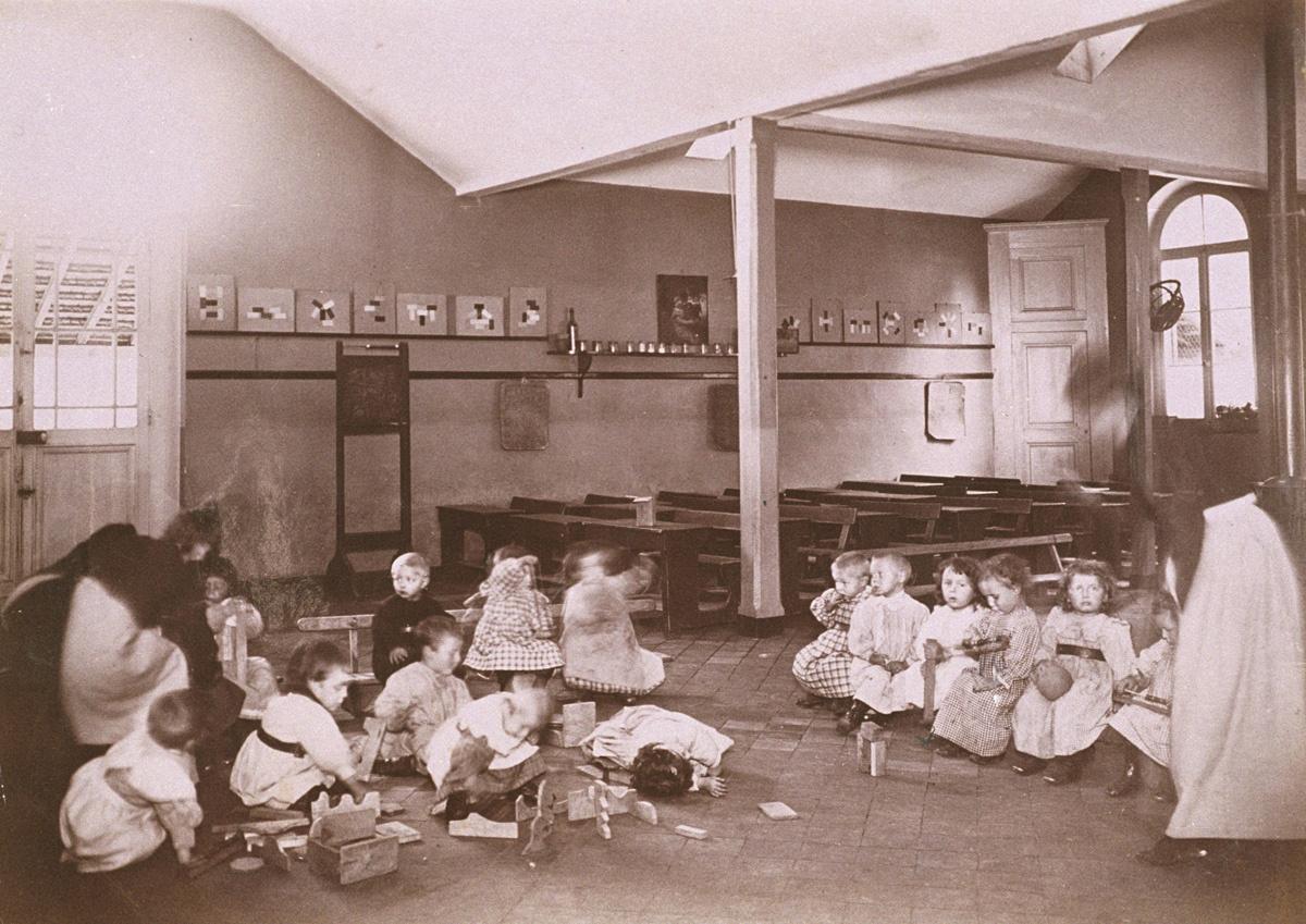 Des enfants jouent au sol dans le pouponnat du Familistère.