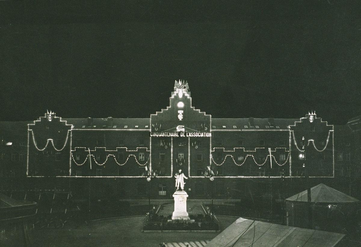 La photographie montre le Palais social illuminé