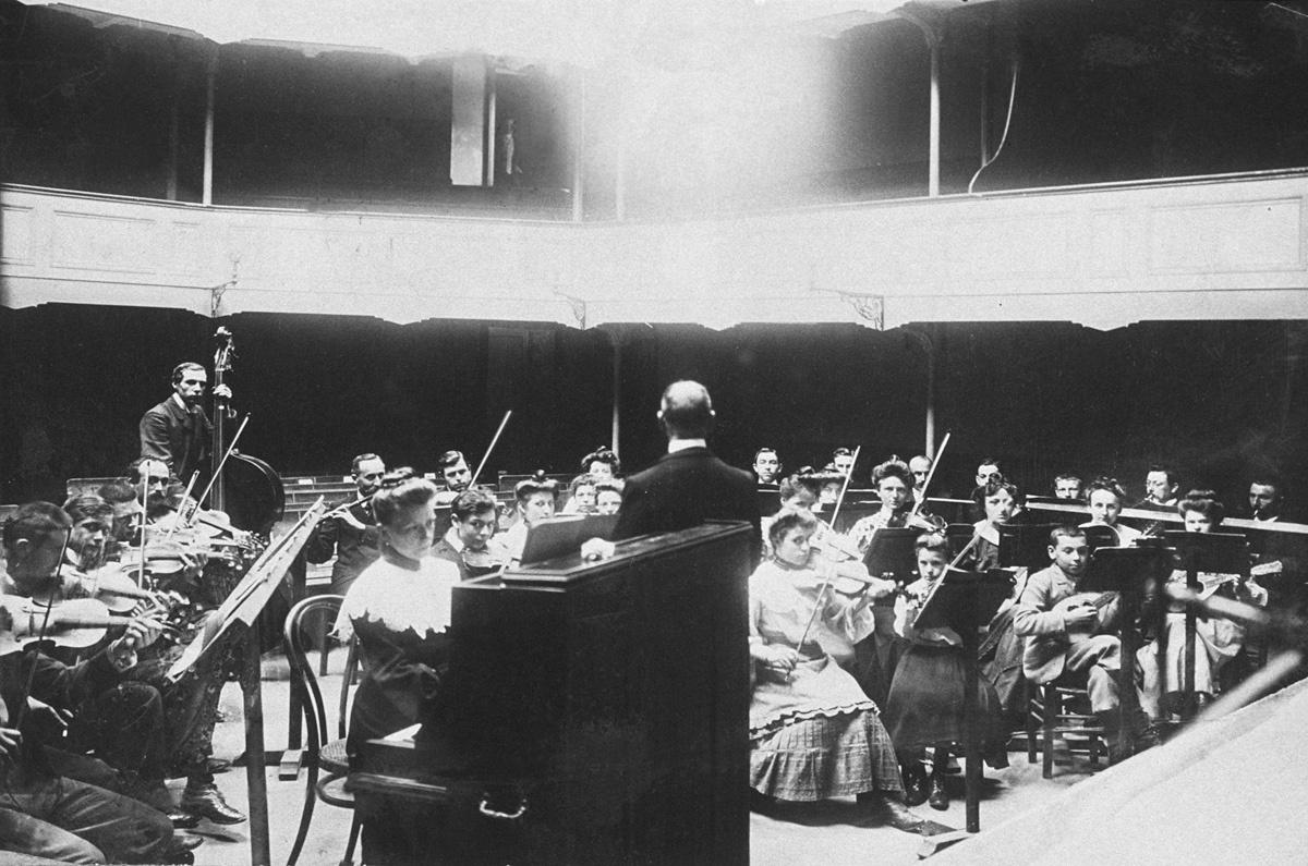 La photographie montre une répétition de l'orchestre au théâtre du Familistère