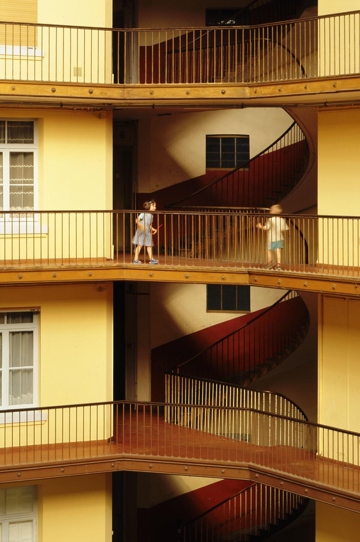 Deux enfants jouent dans la cour de l'aile droite du Palais social.