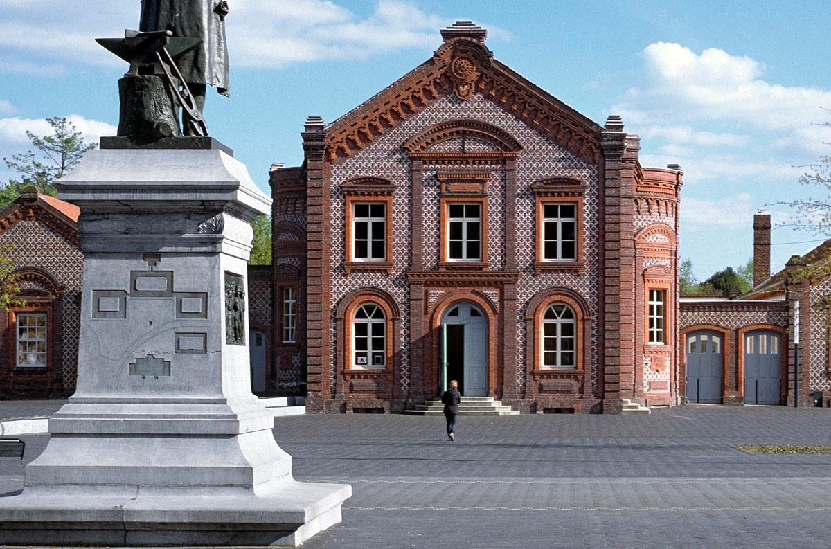 La façade du théâtre du Familistère est vue du piédestal de la statue de Godin.