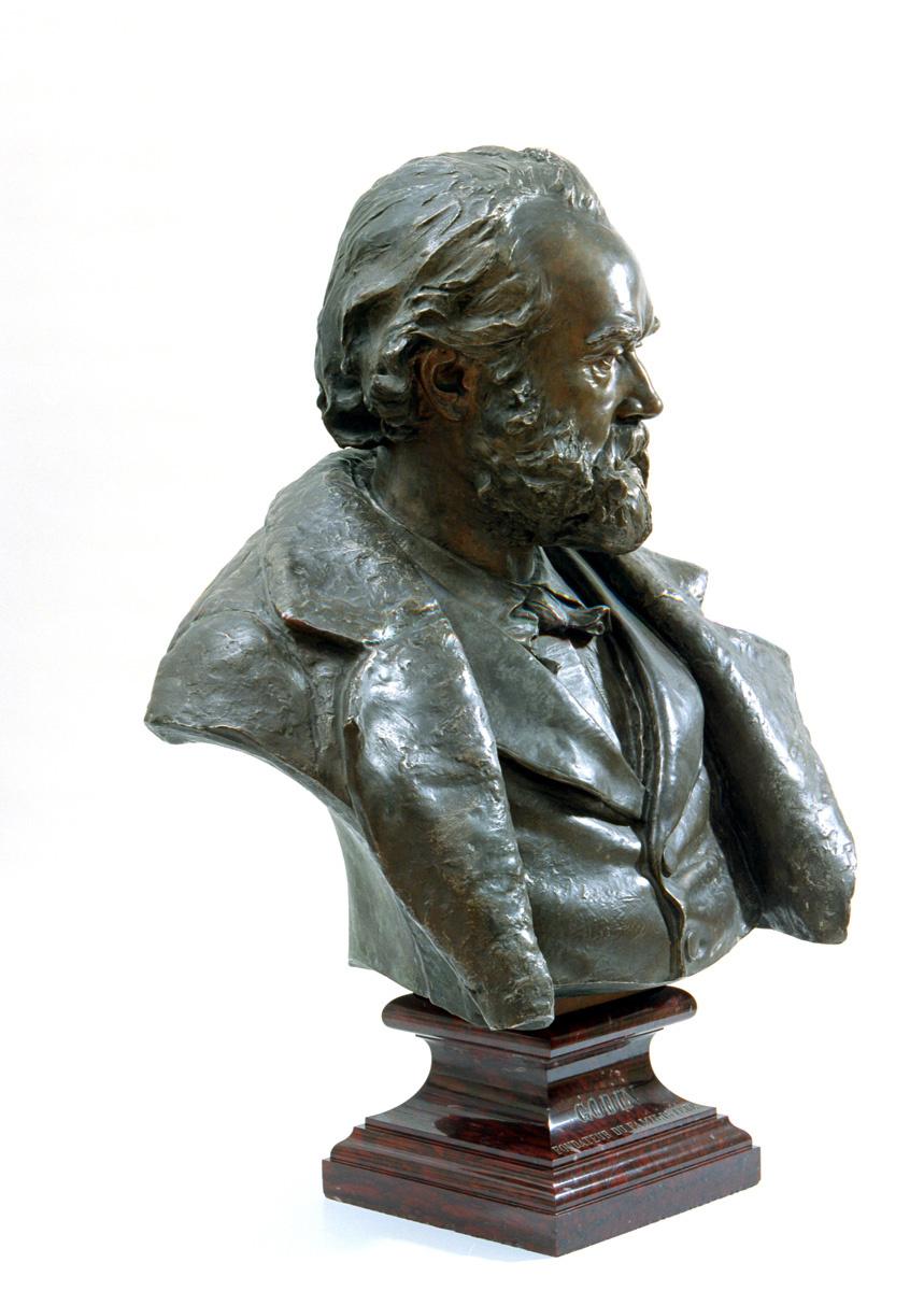 Le portrait en bronze montre Godin en buste, regardant vers la droite.