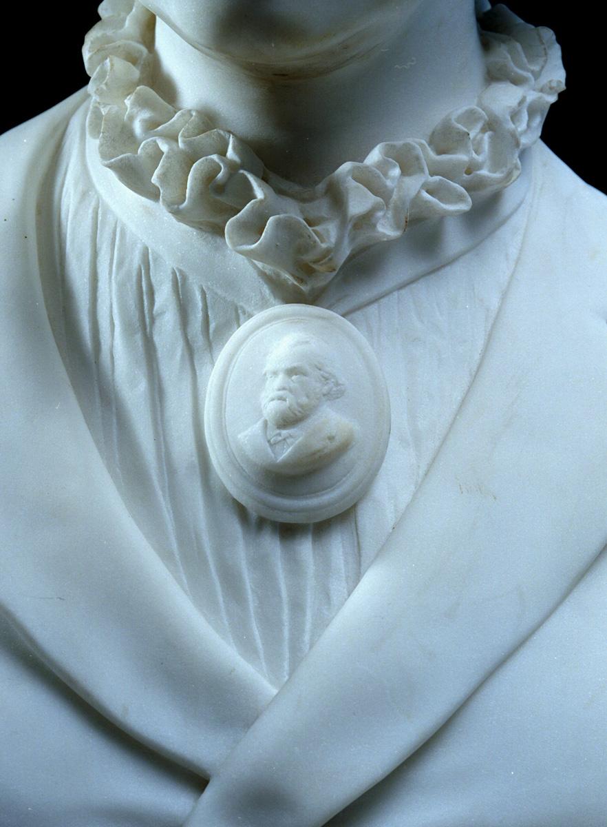 Sur le buste, Marie Moret porte au cou un camée à l'effigie de Godin.