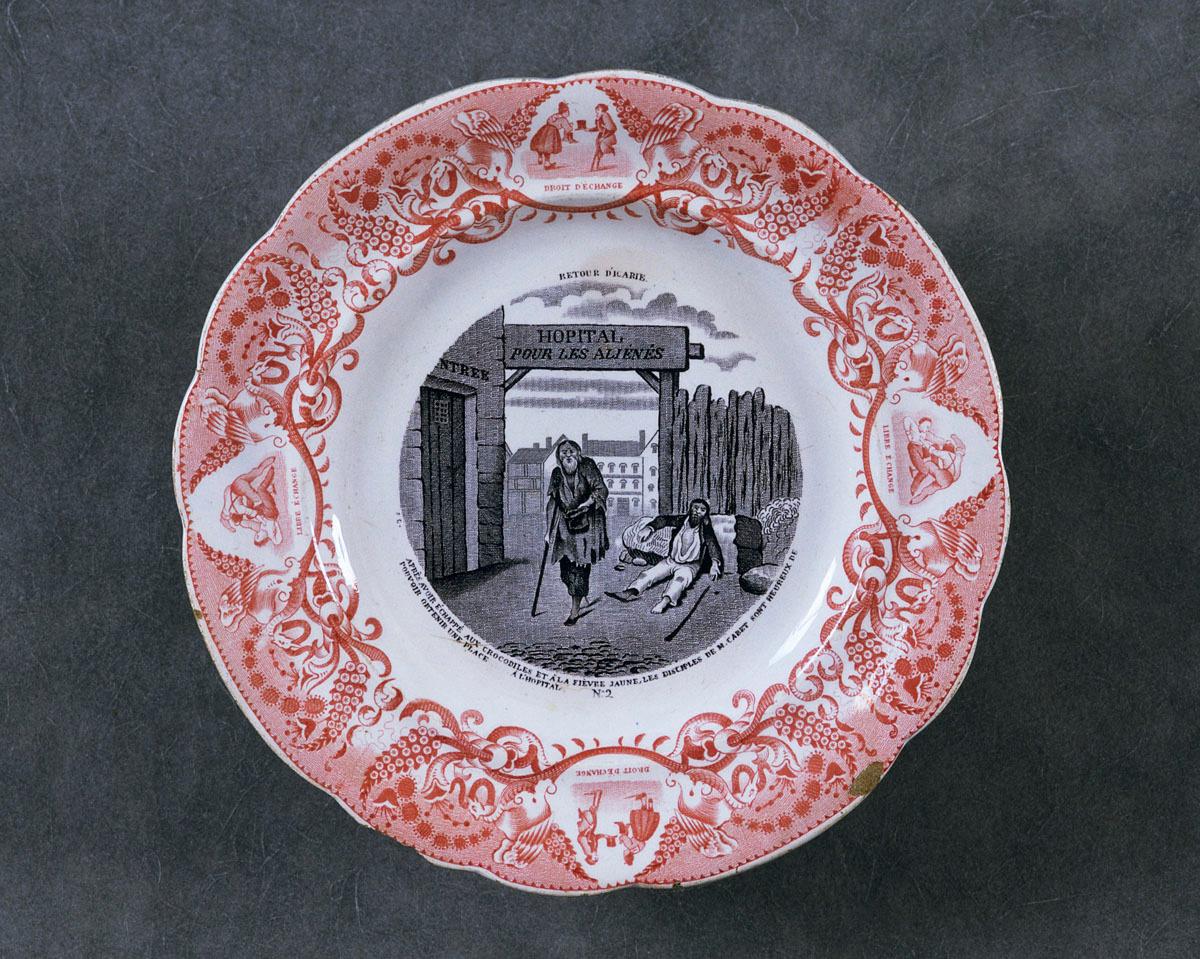 L'assiette est décorée d'une scène satirique sur l'utopie icarienne de Cabet.