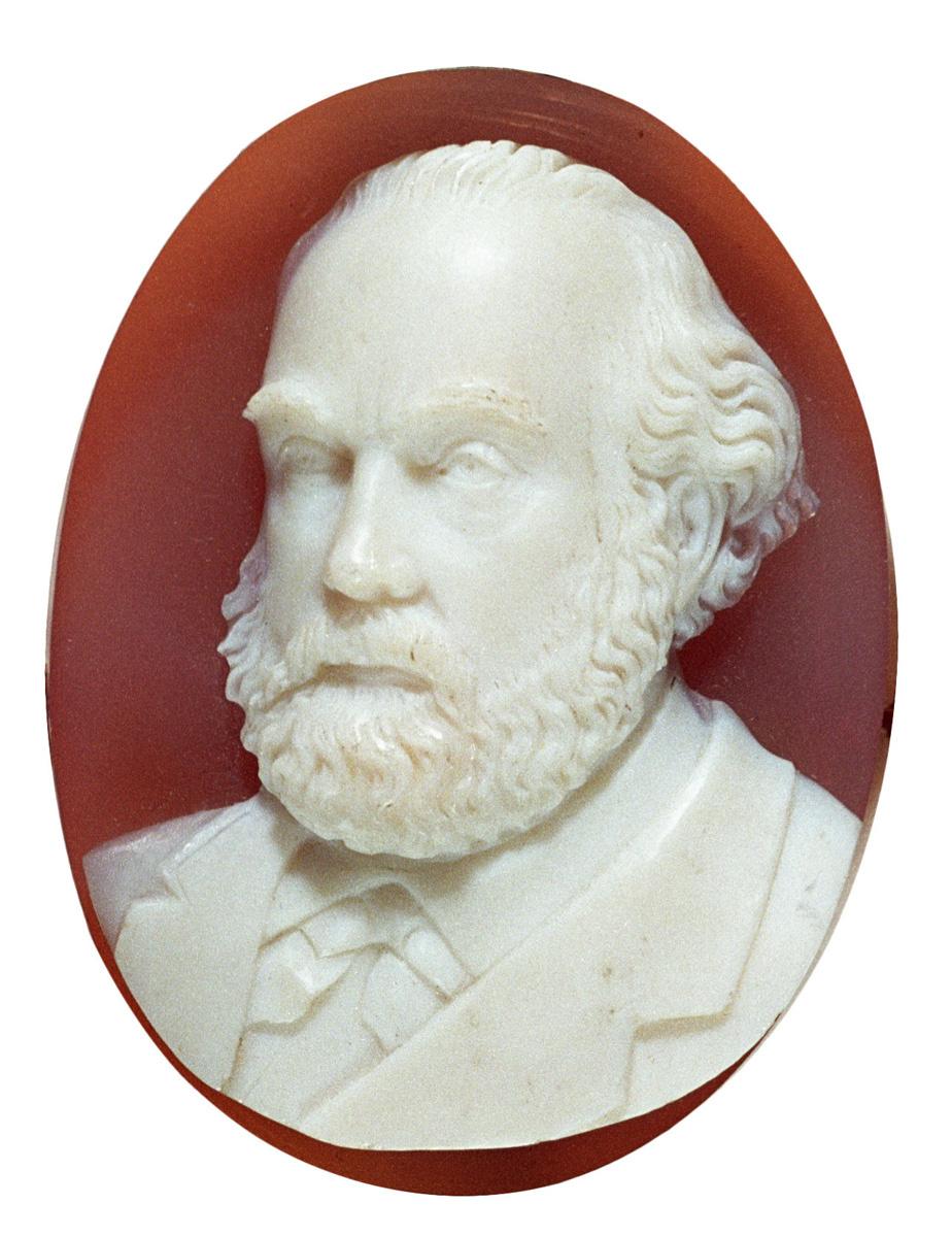 Le médaillon présente un portrait de Godin de trois-quarts, en blanc sur fond ro