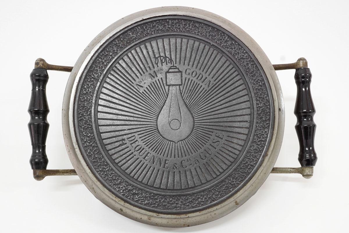 La photographie montre le dessus du chauffe-plat orné d'une ampoule électrique.