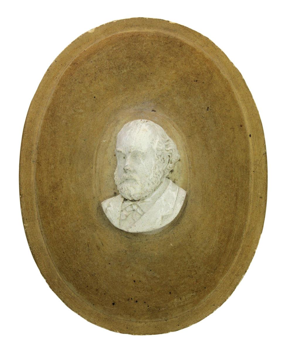 Le portrait en plâtre de Godin est fixé sur un médaillon en bois ovale.