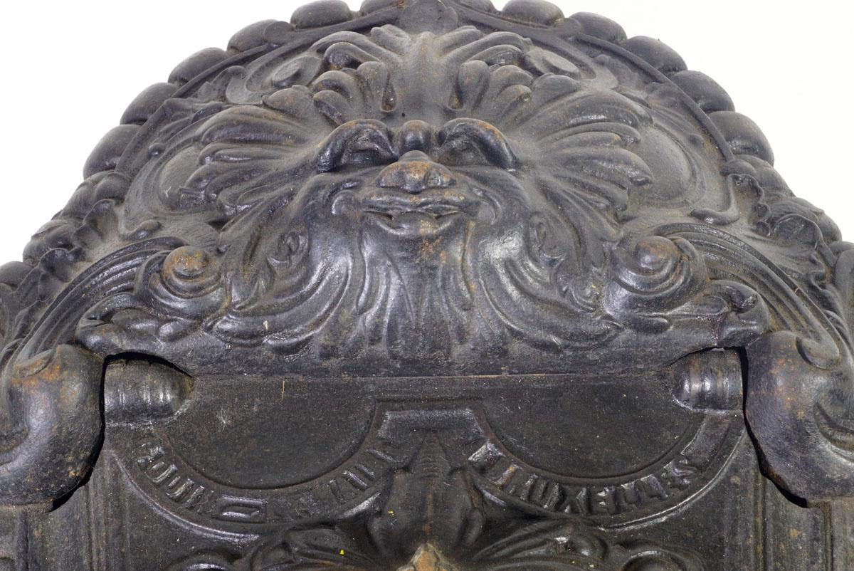 La photographie montre le détail du masque sur le dessus du bac à charbon.