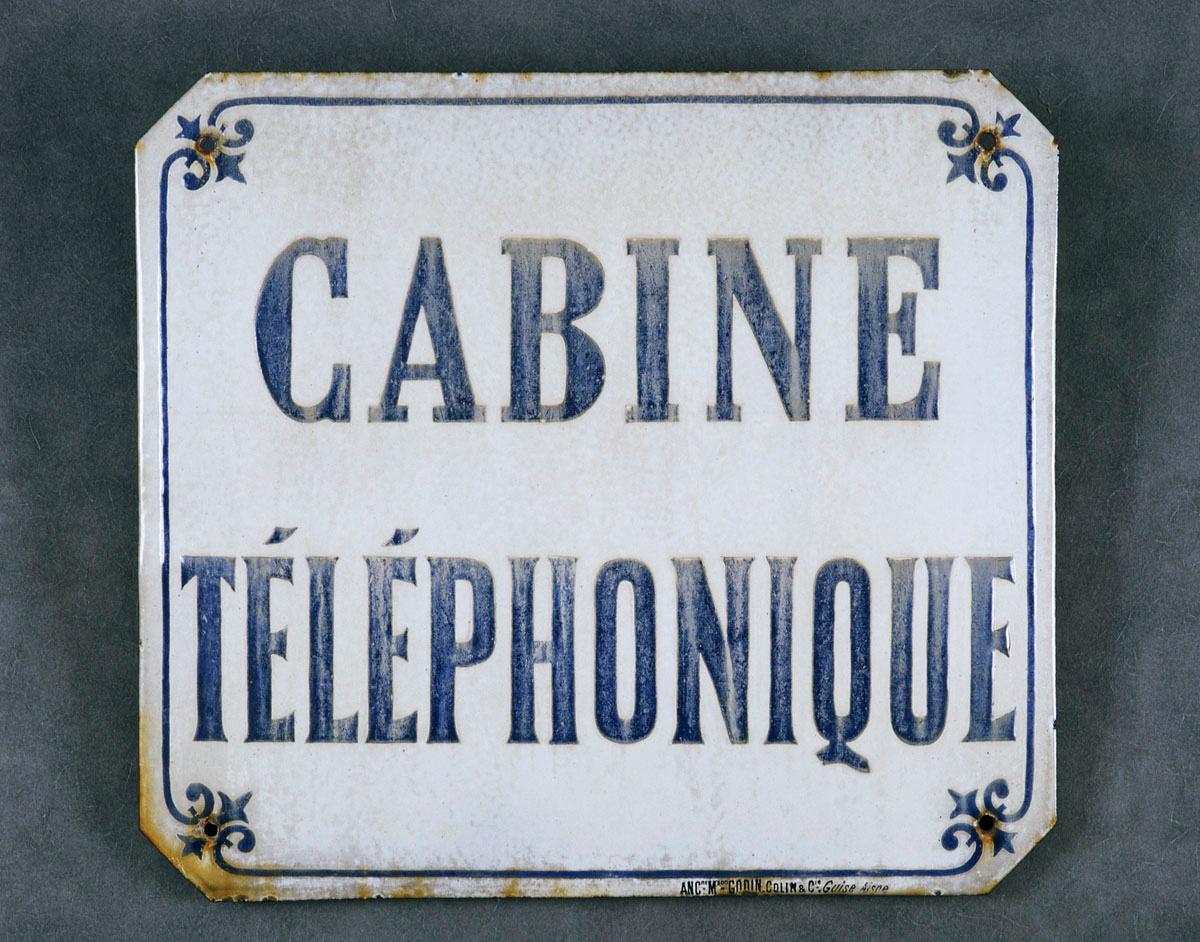 La plaque indicative présente un texte bleu sur fond ivoire.