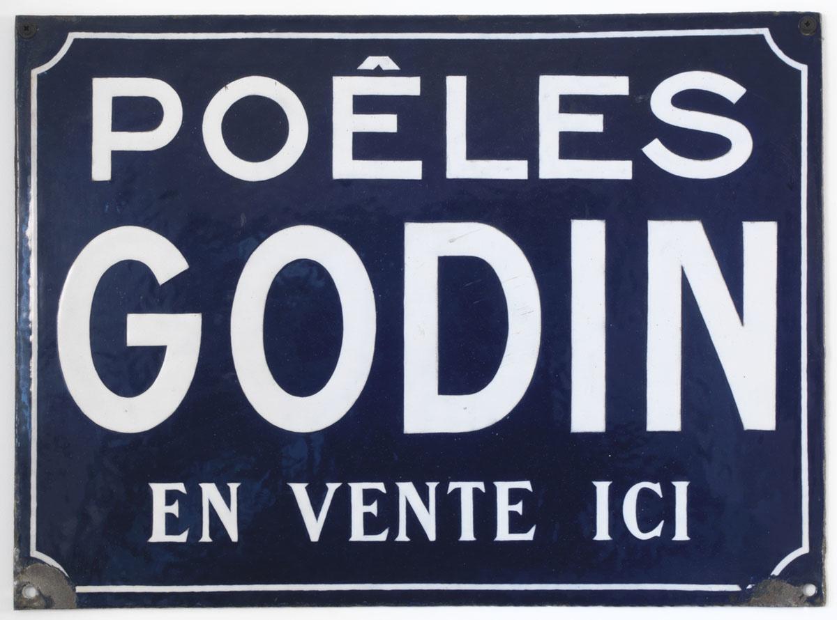 La plaque indicative présente un texte blanc sur fond bleu.