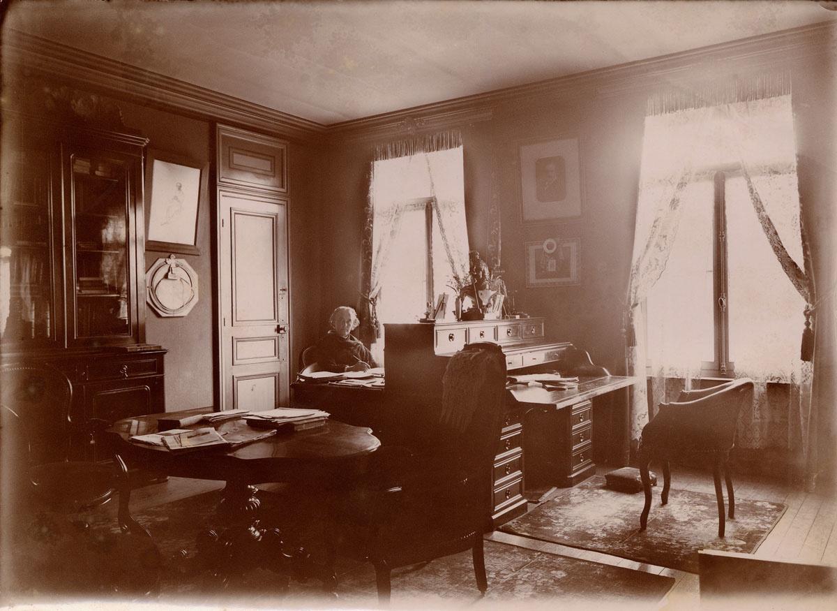 La photographie montre Marie Moret assise devant son bureau.