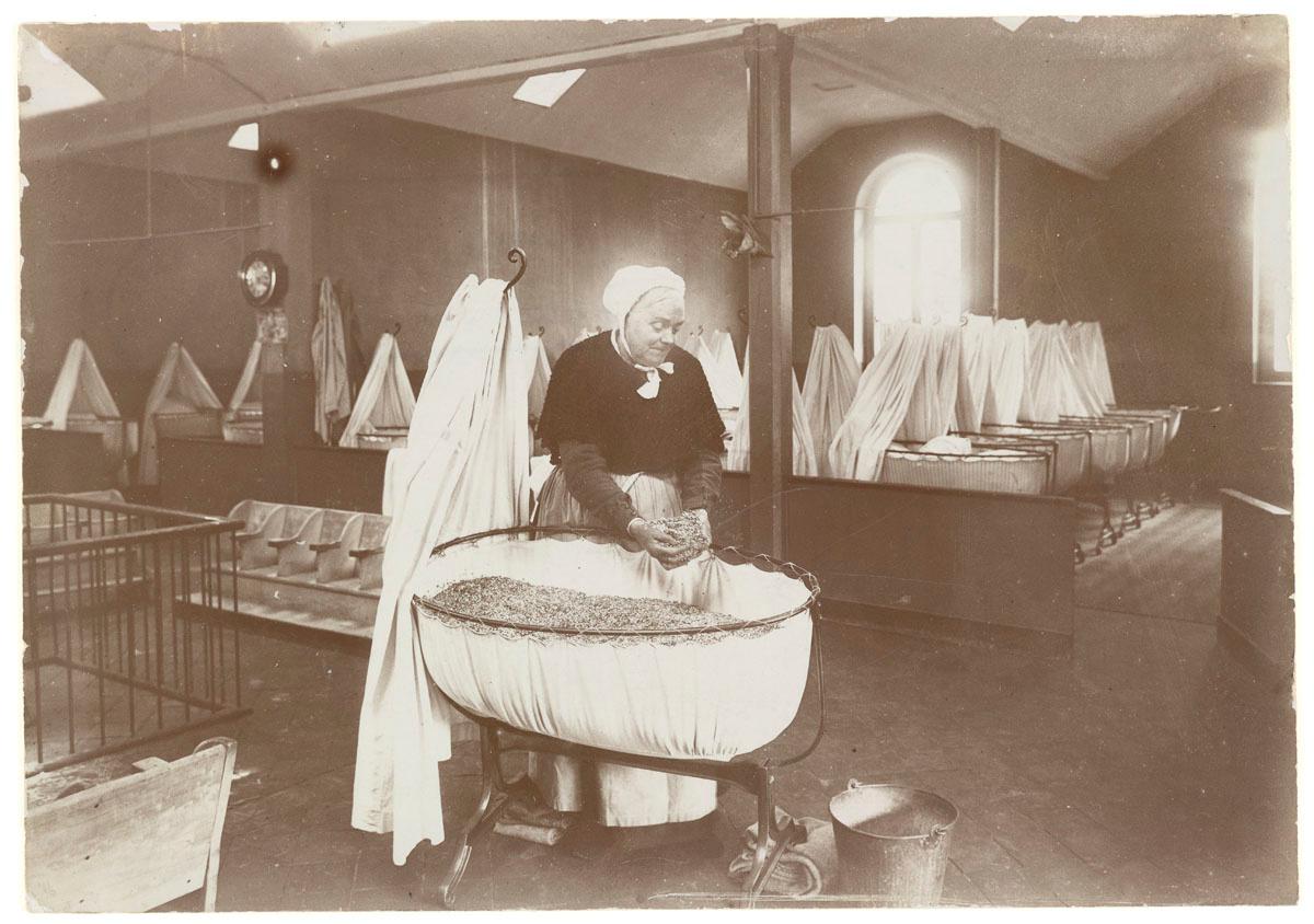 La photographie montre Madame Roger préparant le matelas d'un berceau.