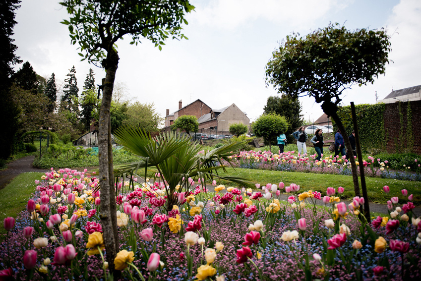 Un massif de felurs dans le jardin d'agrément et quelques visiteurs en arrière p