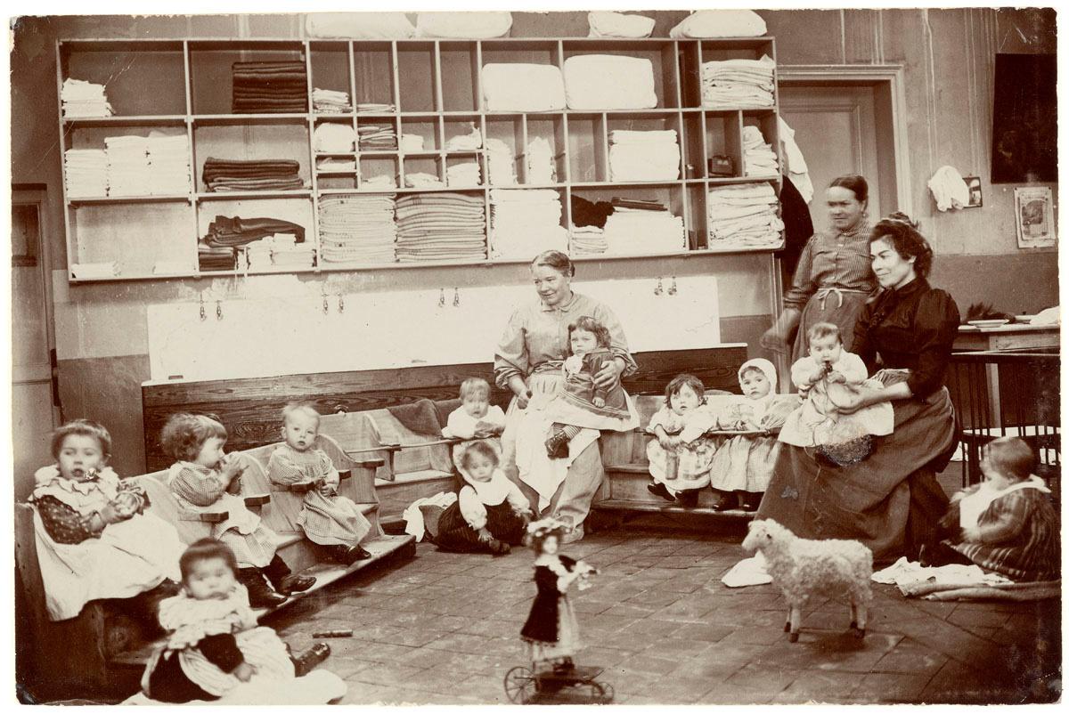 La photographie met en scène des nourrissons et leurs nourrices dans la crèche d