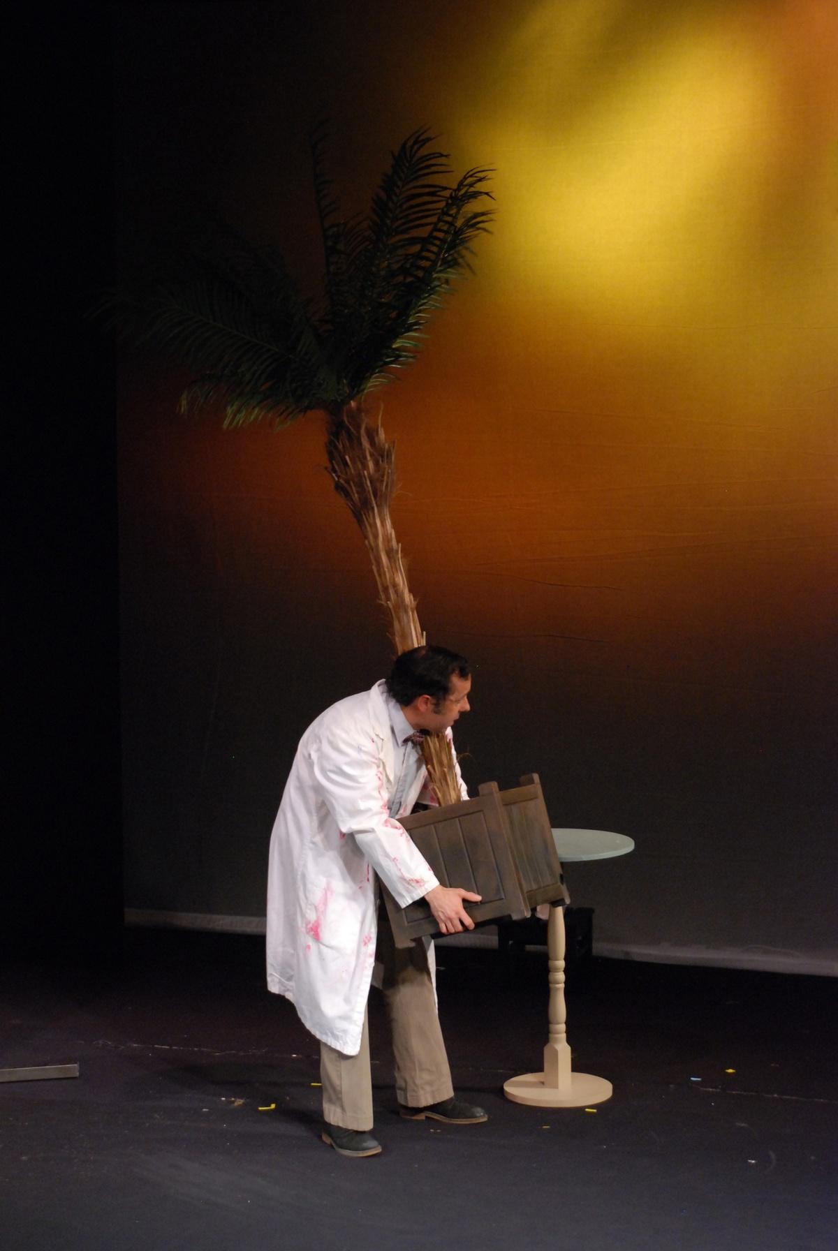 Un homme sur scène en blouse blanche transporte une grosse plante.