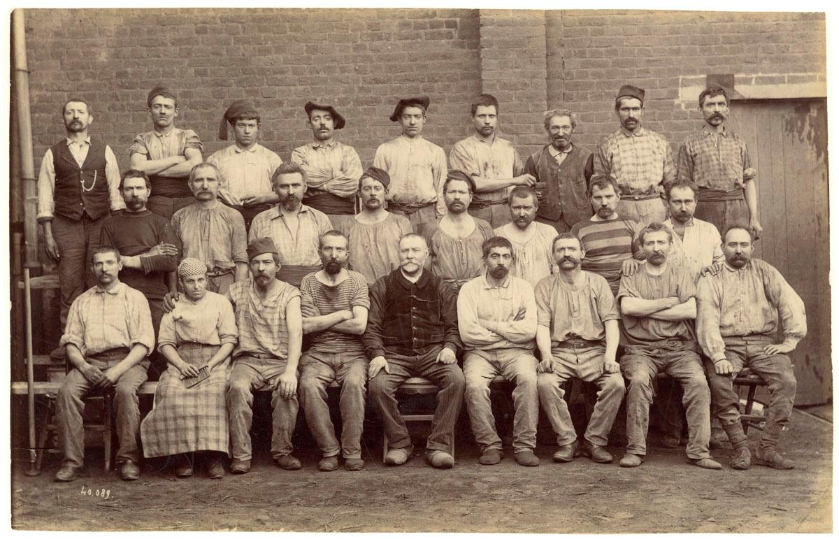 La photographie montre un groupe d'ouvriers de la fonderie du Familistère avec u