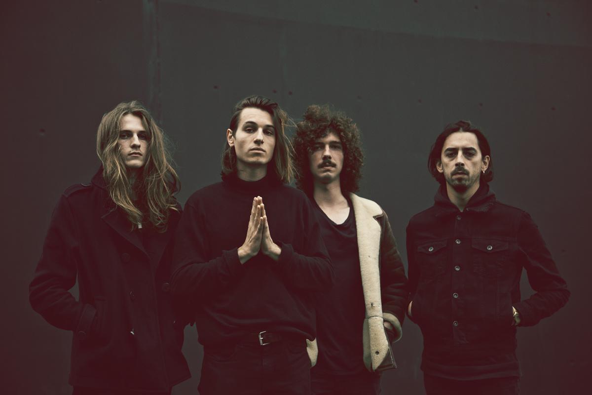 Quatre hommes alignés, habillés en noir sur fond sombre.