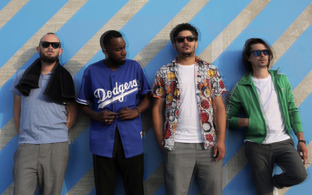 Quatre hommes, sur un fond gris et bleu ciel, habillés avec des couleurs vives.