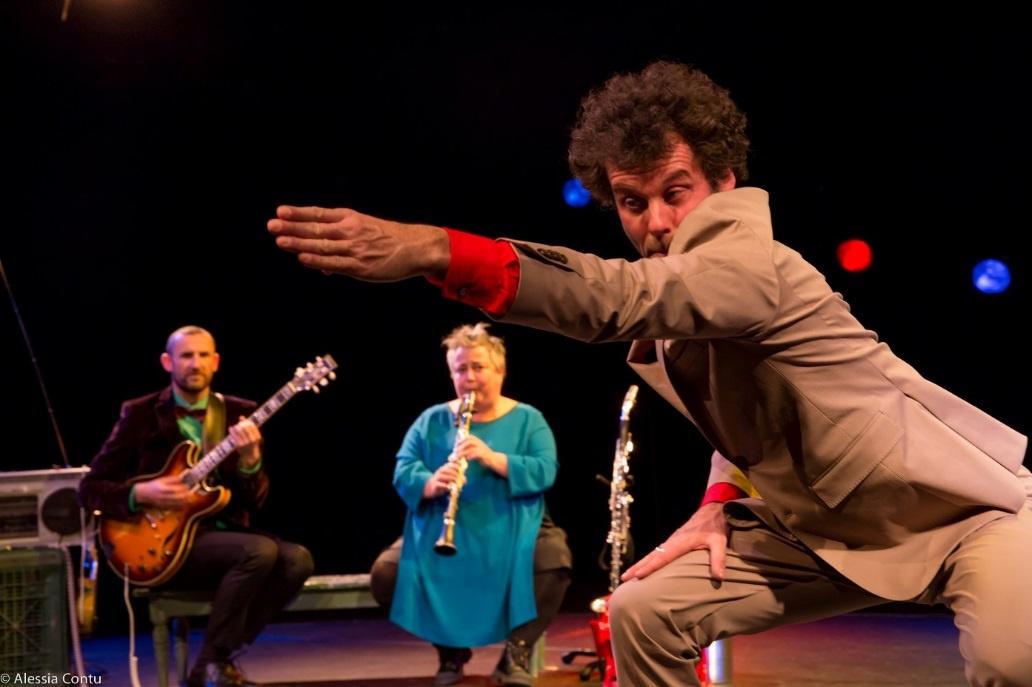 Un orchestre en arrière plan et un homme en costume des années 70 faisant un ges