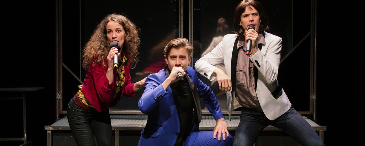Une femmes et deux hommes chantent en tenant un micro. Ils ont un look années 70