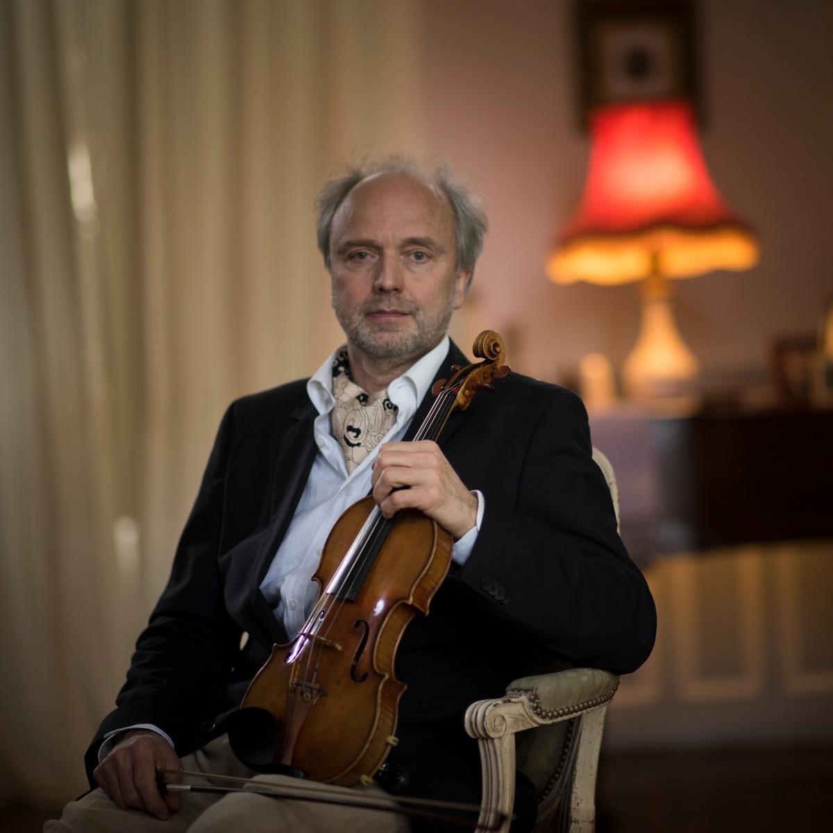 Un homme assis dans un salon, un violon à la main.