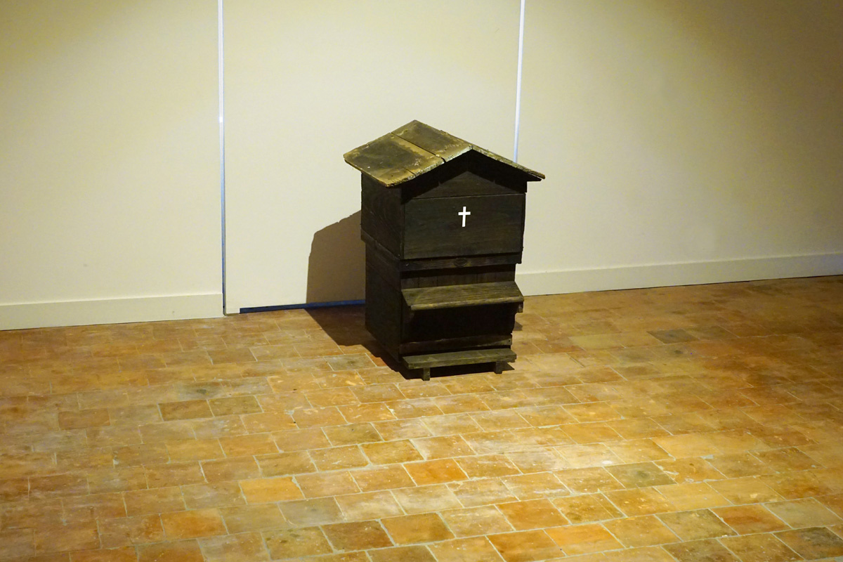 La photographie montre une ruche noire frappée d'une croix blanche.