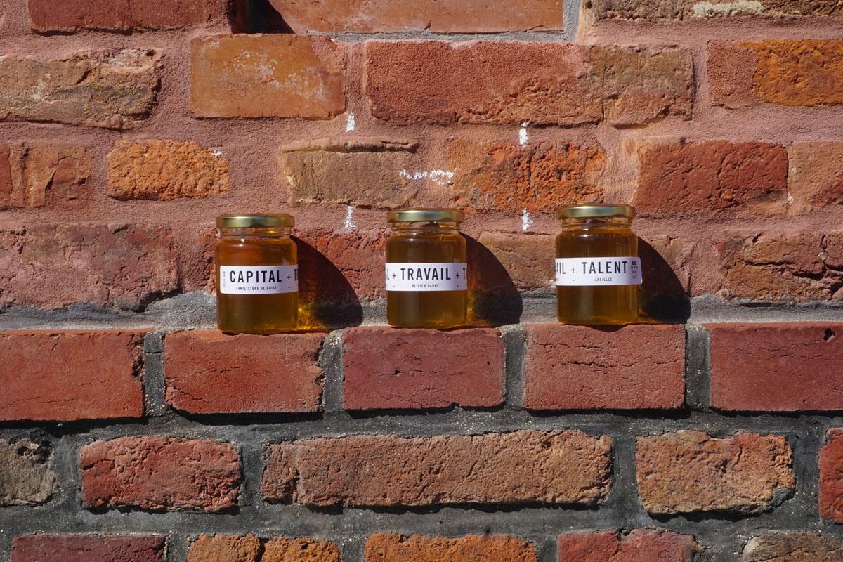La photographie montre trois pots de miel étiquetés sur fond de briques du Famil