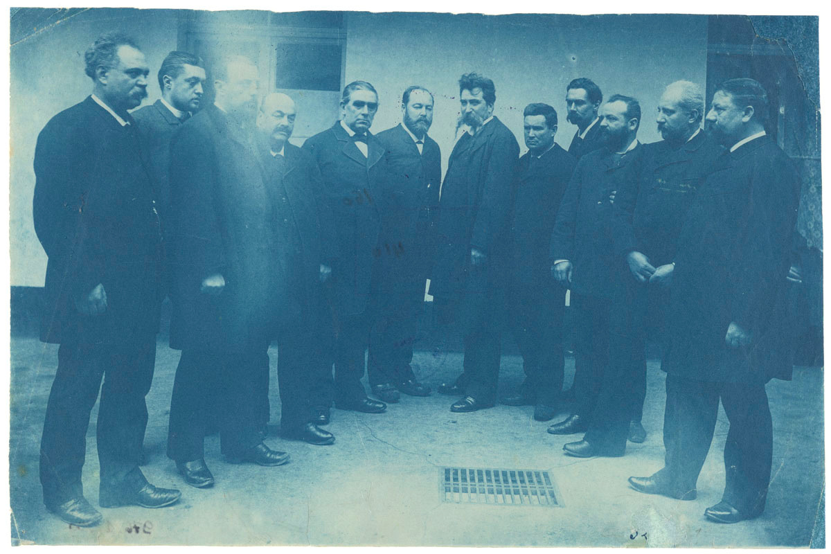 La photographie de couleur bleu est un portrait collectif d'hommes dans une cour