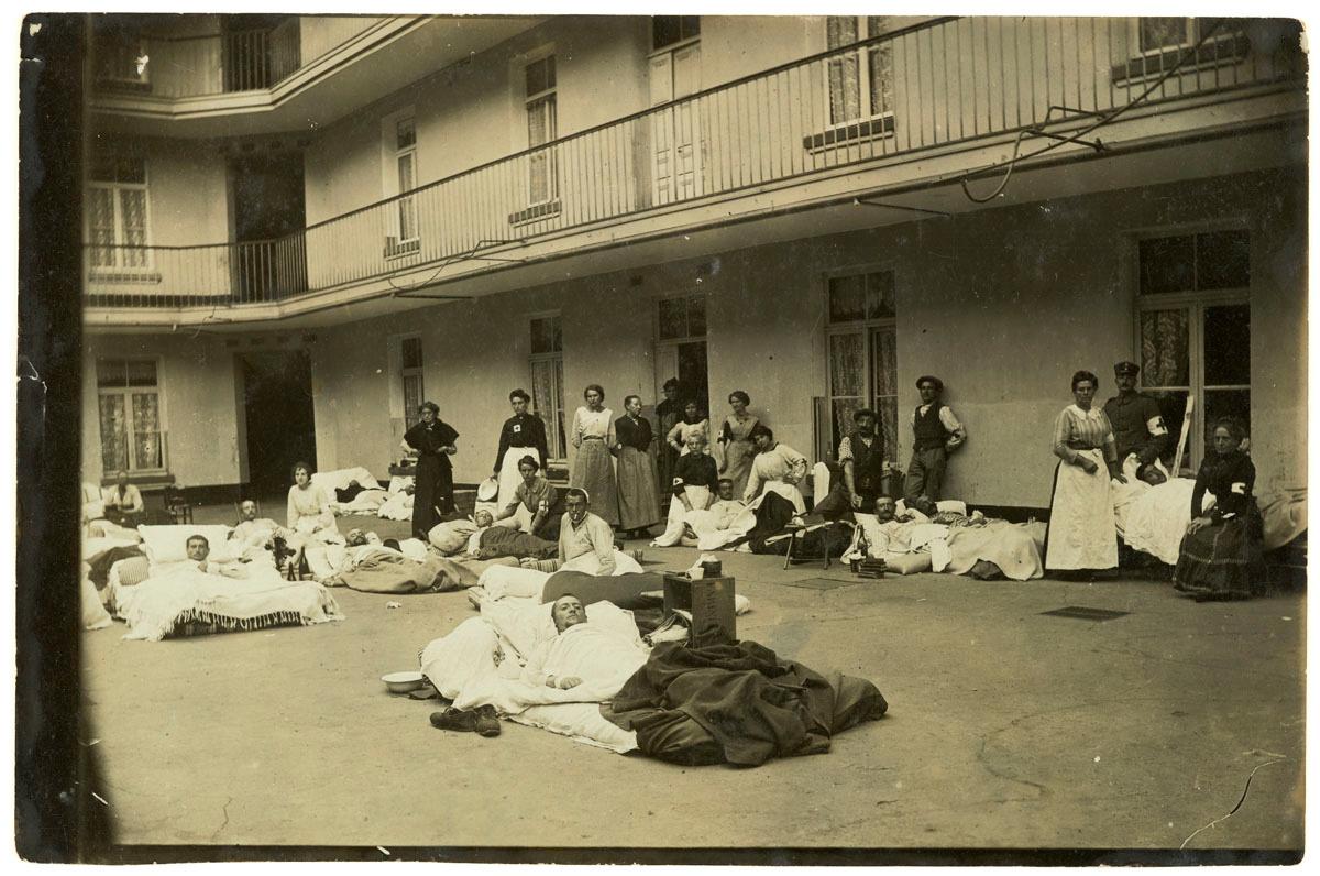 La photographie montre des soldats blessés couchés dans la cour