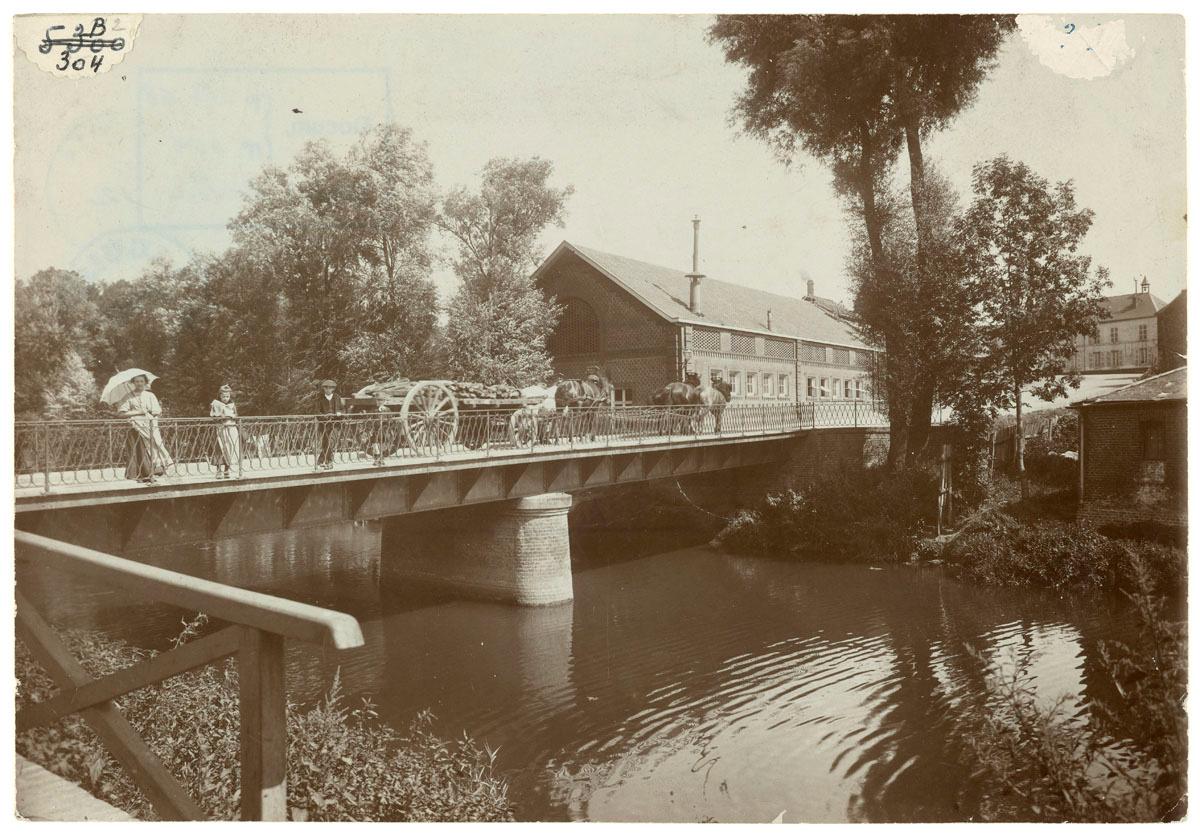 La photographie montre le pont sur l'Oise du Familistère.