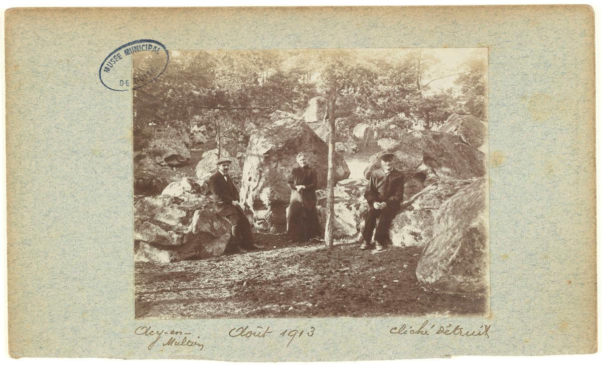 La photographie montre trois personnage posant dans la nature.