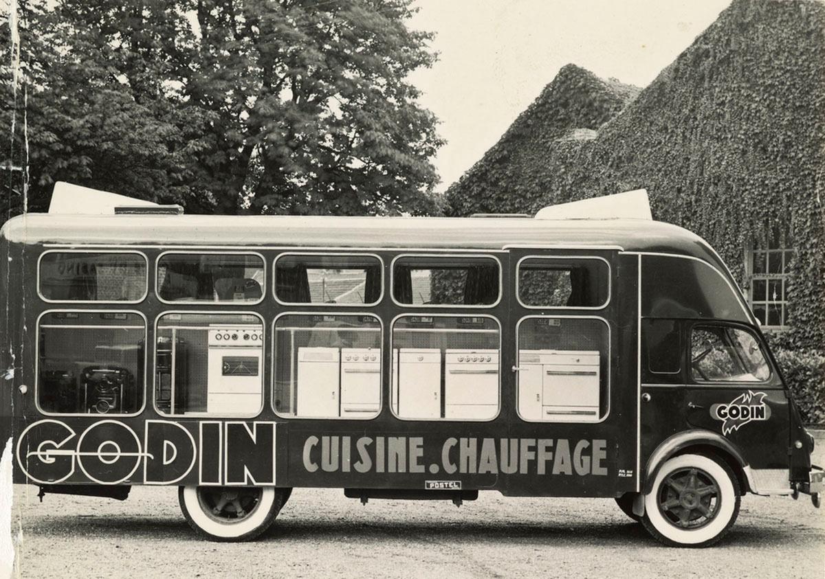 La photographie montre un camion publicitaire devant le théâtre du Familistère.