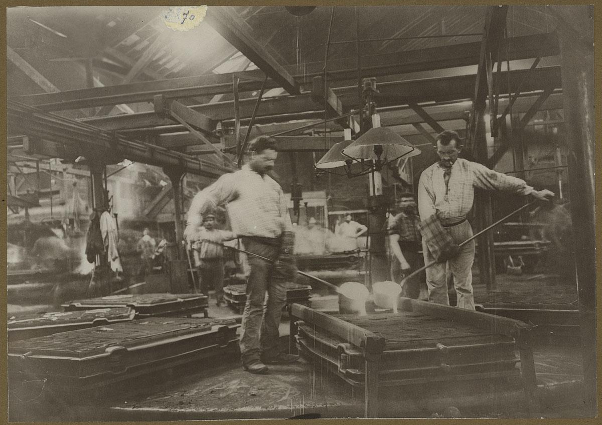 La photographie montre deux mouleurs en activité dans l'usine du Familistère.