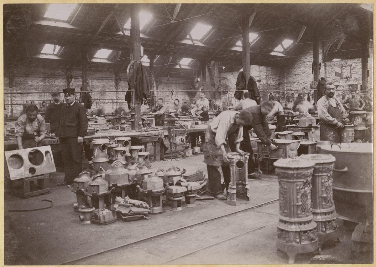 La photographie montre des monteurs au travail dans l'usine du Familistère