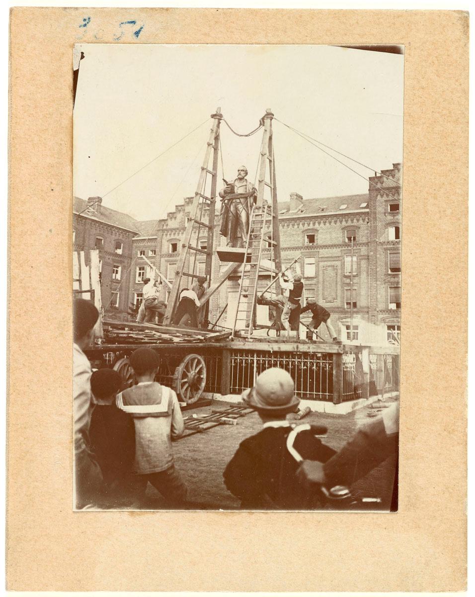 La photographie montre l'installation de la statue sur son piédestal