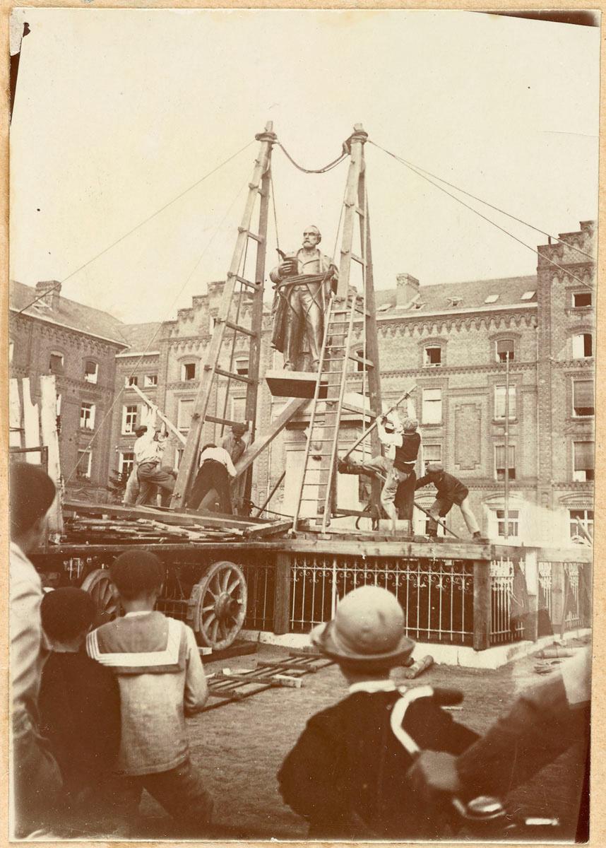 La photographie montre l'installation de la statue sur son piédestal.