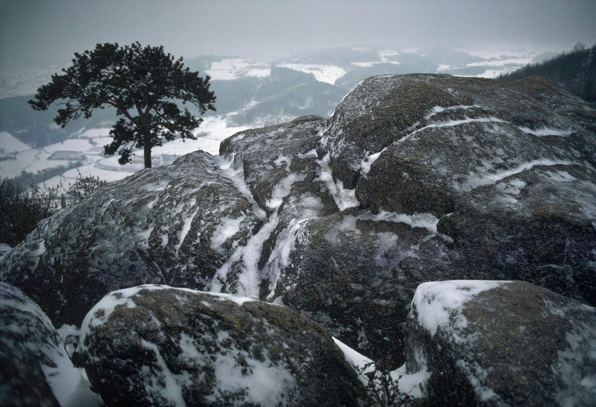 La photographie montre des rochers enneigés.