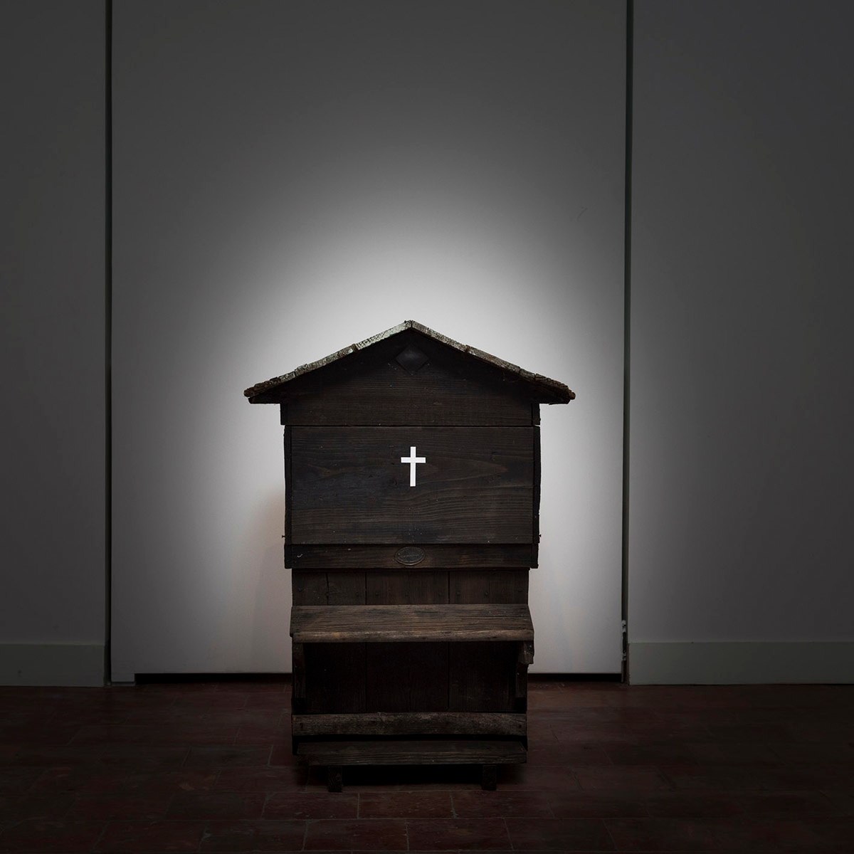 La photographie montre une ruche sombre ornée d'une croix blanche