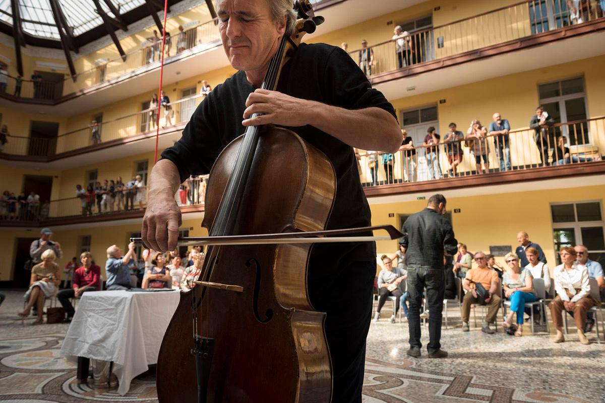 La photographie montre un violoncelliste dans la cour du pavillon central.