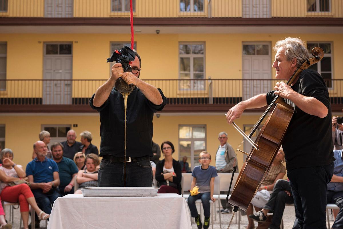 La photographie montre un violoncelliste et Olivier Darné pressant du miel