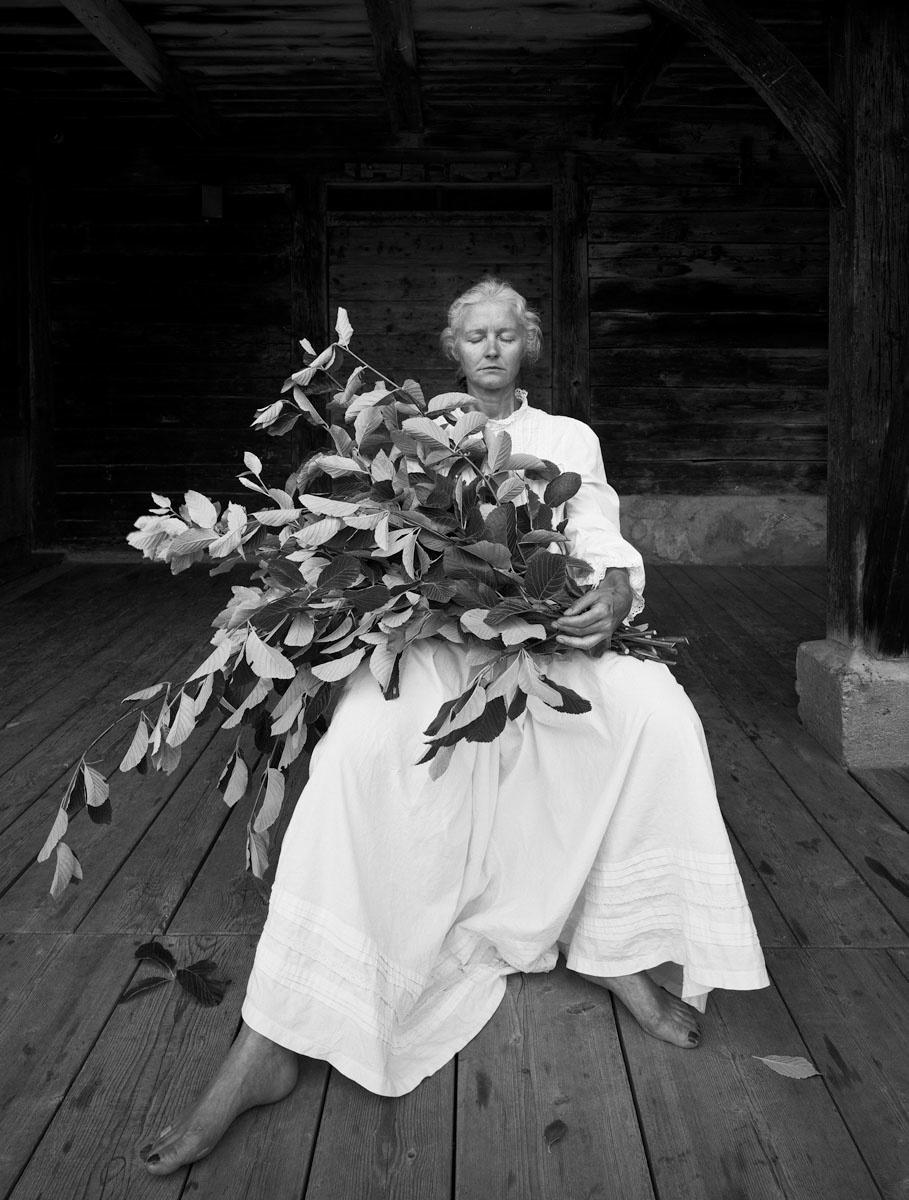 La photographie montre une femme assise en robe blanche avec un bouquet de feuil