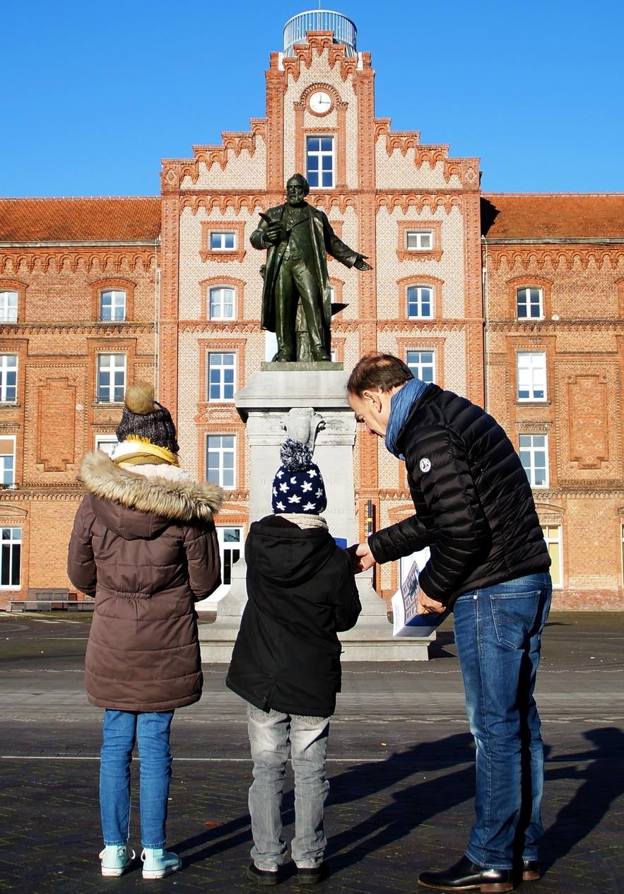 Un grand-père et ses deux petits-enfants sur la place du Familistère.