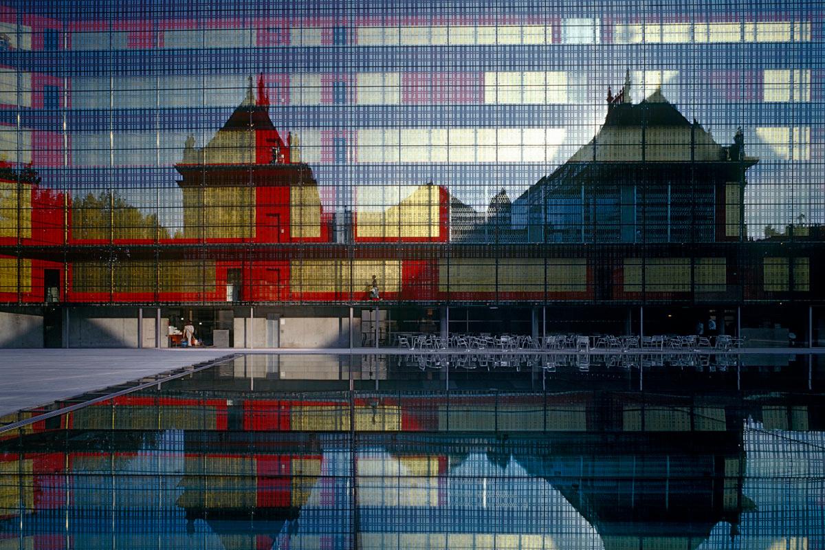 La photographie montrer le reflet d'un bâtiment sur une façade de verre