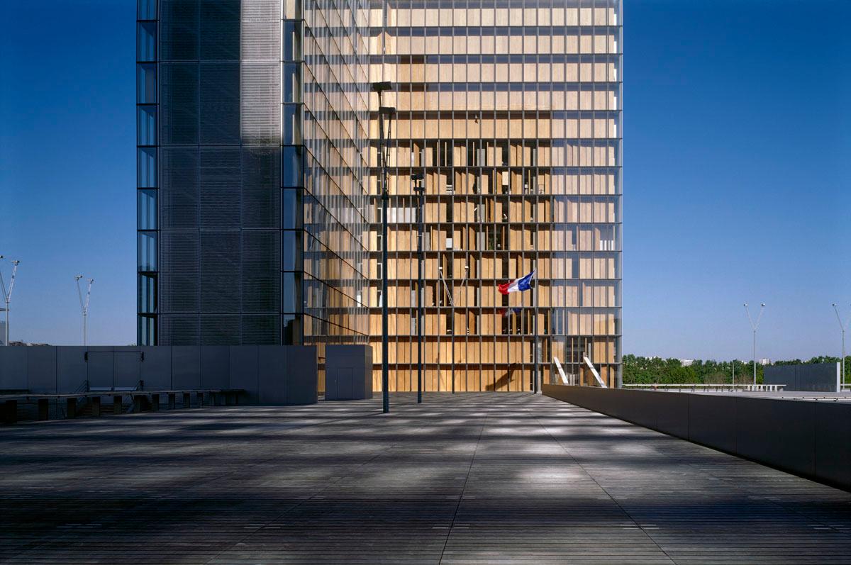 La photographie montre un drapeau tricolore devant une tour de la Bibliothèque n